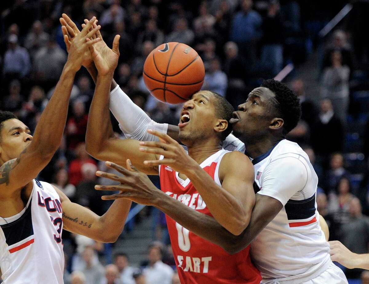 Sacred Heart's Jordan Allen (0) vies for the ball with Connecticut's Shonn Miller, left, and Amida Brimah