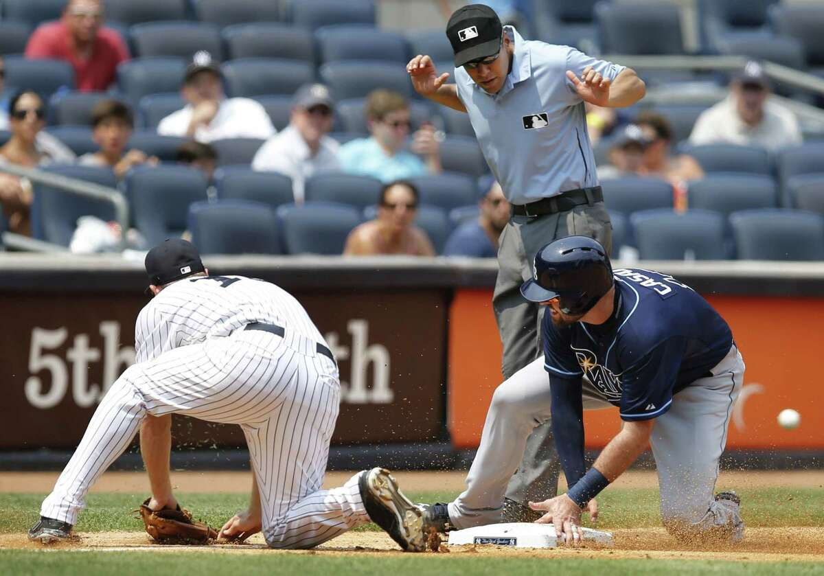 New York Yankees starter Ivan Nova's errant throw skips away from third baseman Chase Headley, left, as Tampa Bay Rays' Curt Casali, right, and umpire Gabe Morales, center, react in the fifth inning of Sunday's game at Yankee Stadium in New York. Casali scored on the error.
