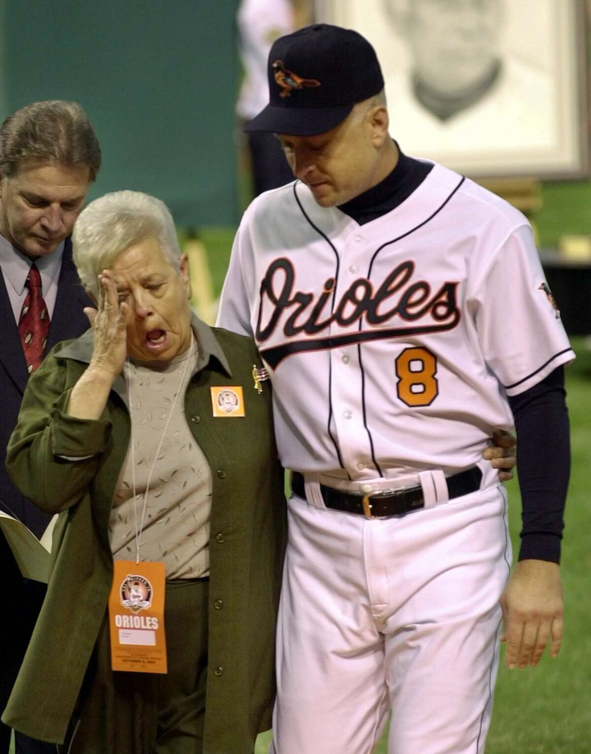 This Oct. 6, 2001 photo shows Cal Ripken escorting his mother, Vi, from the field, after throwing out the ceremonial first pitch before Cal's final game, at Oriole Park in Baltimore.