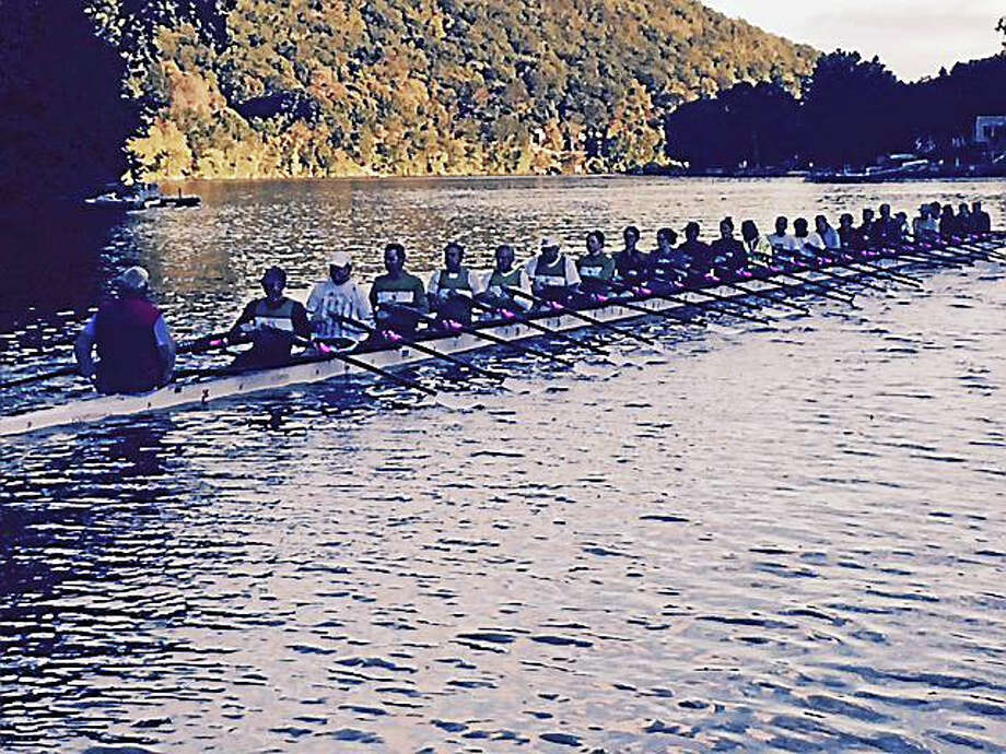 Members of the New Haven Rowing Club and the Yale graduate students row in the world's largest sculling boat. Photo: David Borges — Register