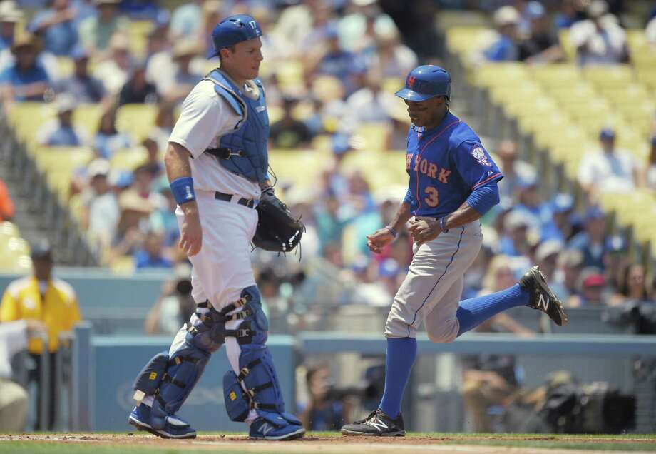 New York Mets' Curtis Granderson, right, scores on a single by Wilmer Flores as Los Angeles Dodgers catcher A.J. Ellis watches during the first inning of a baseball game, Sunday, July 5, 2015, in Los Angeles. (AP Photo/Mark J. Terrill) Photo: The Associated Press   / AP