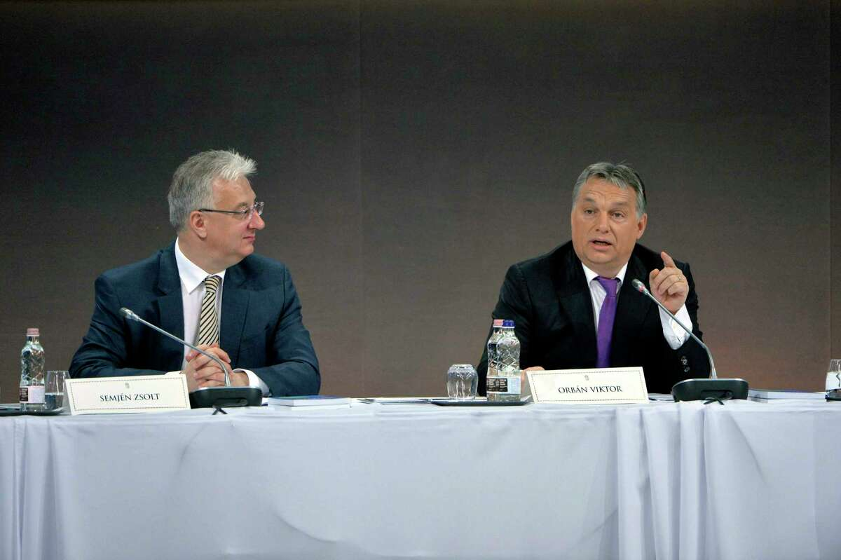 Hungarian Prime Minister Viktor Orban, right, addresses a session of the Hungarian Diaspora Council, an organization of Hungarians living dispersed all over the world, as Deputy PM in charge of national politics Zsolt Semjen looks on in Budapest, Hungary, Wednesday, Dec. 2, 2015. Orban says he believe a secret pact led by Germany to bring up to 500,000 Syrians from Turkey directly into the European Union to be revealed soon.