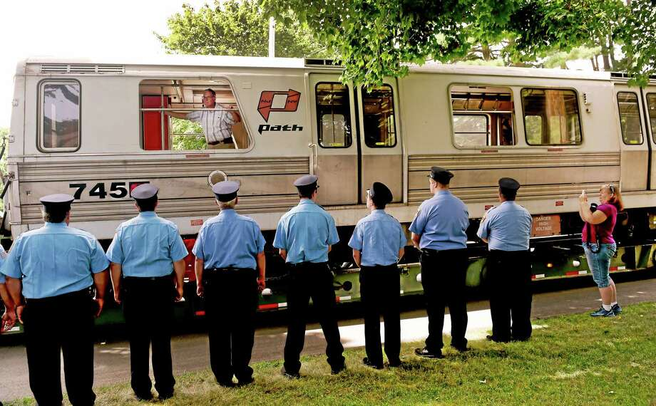 North Branford firefighters stand at attention as PATH Car 745, which was in the PATH station under the north tower of the World Trade Center and survived the Sept. 11, 2001, terrorist attack on New York, is received at the Shore Line Trolley Museum. Thursday in East Haven. Photo: Peter Hvizdak — New Haven Register   / ©2015 Peter Hvizdak
