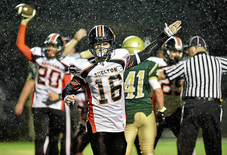 Shelton's Anthony Schiavo signals first down as Michael Casinelli (20) celebrates with teh ball behind him during Shelton's 17-7 victory over Notre Dame-West Haven. Photo: Photo By Catherine Avalone -- New Haven Register   / Catherine Avalone/New Haven Register