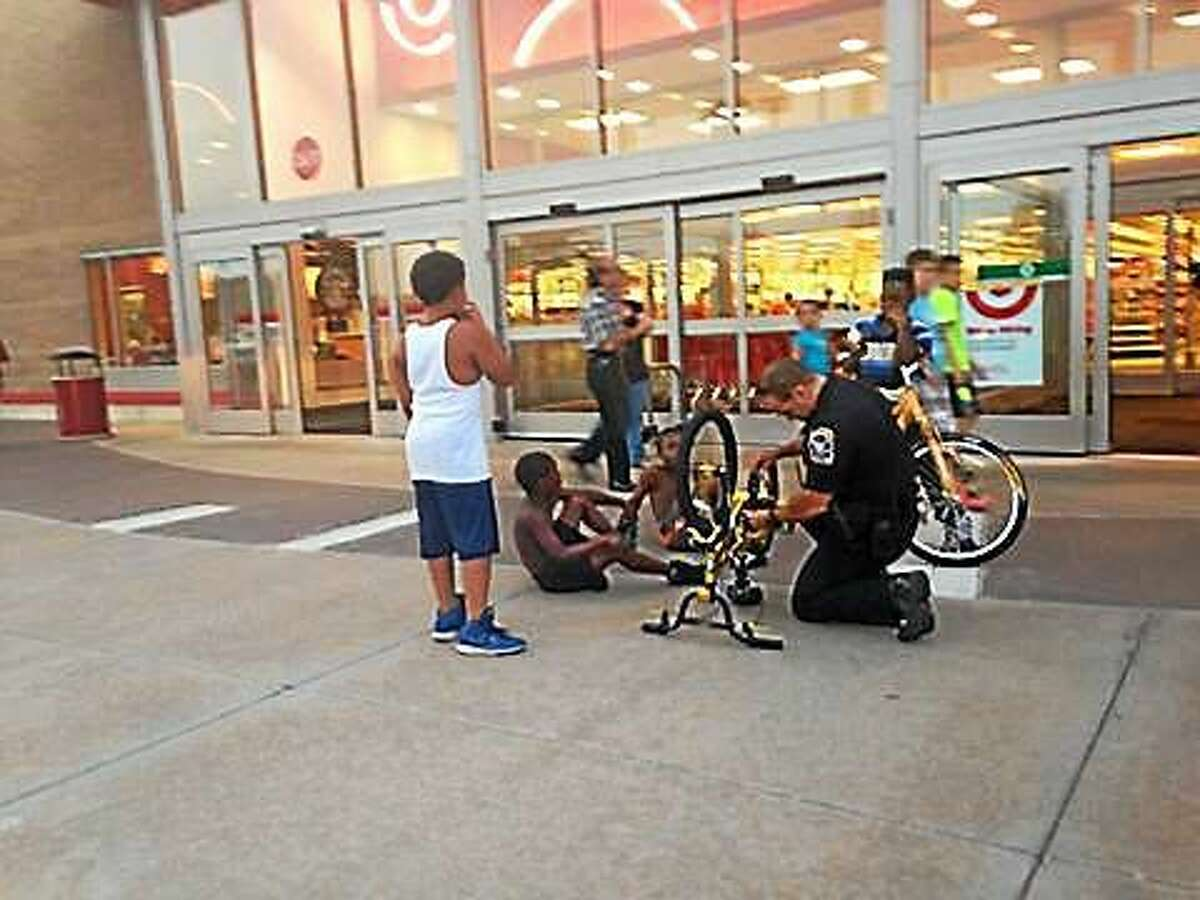 This photo taken by Shelton resident Faith Bisson Taylor shows Ansonia police Officer Michael Castillo helping a local youth in front of the Target store.