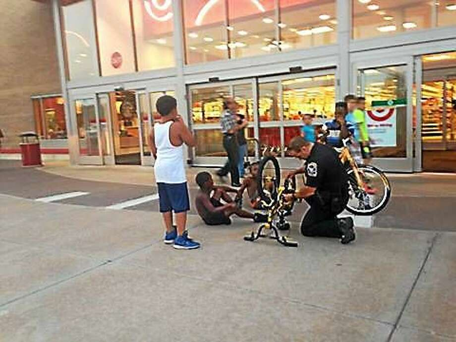 This photo taken by Shelton resident Faith Bisson Taylor shows Ansonia police Officer Michael Castillo helping a local youth in front of the Target store. Photo: FACEBOOK