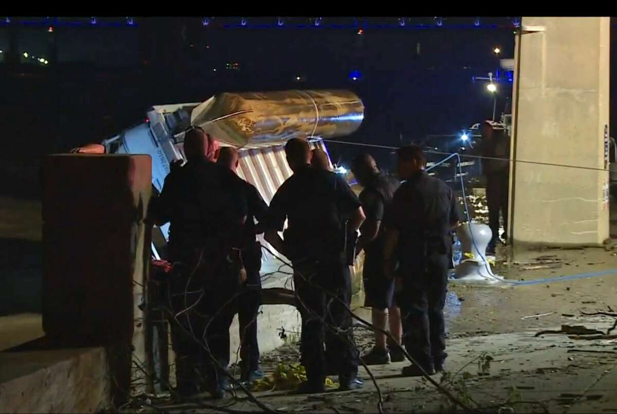 In this image taken from video, police officers look on as an overturned pontoon boat is pulled out of the water of the Ohio River on July 4, 2015, in Louisville, Ky. Kentucky authorities say two people have been killed and three remain missing after the boat they were riding in hit the Clark Memorial Bridge and capsized in the Ohio River.
