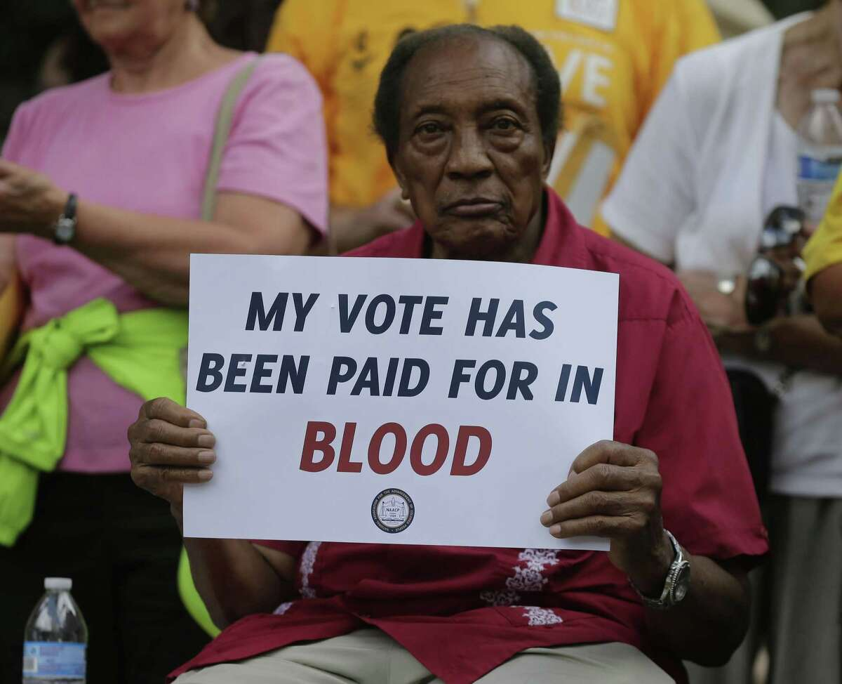 A man holds a protest sign at a rally in Winston-Salem, N.C. on July 13, 2015 after the beginning of a federal voting rights trial challenging a 2013 state law.