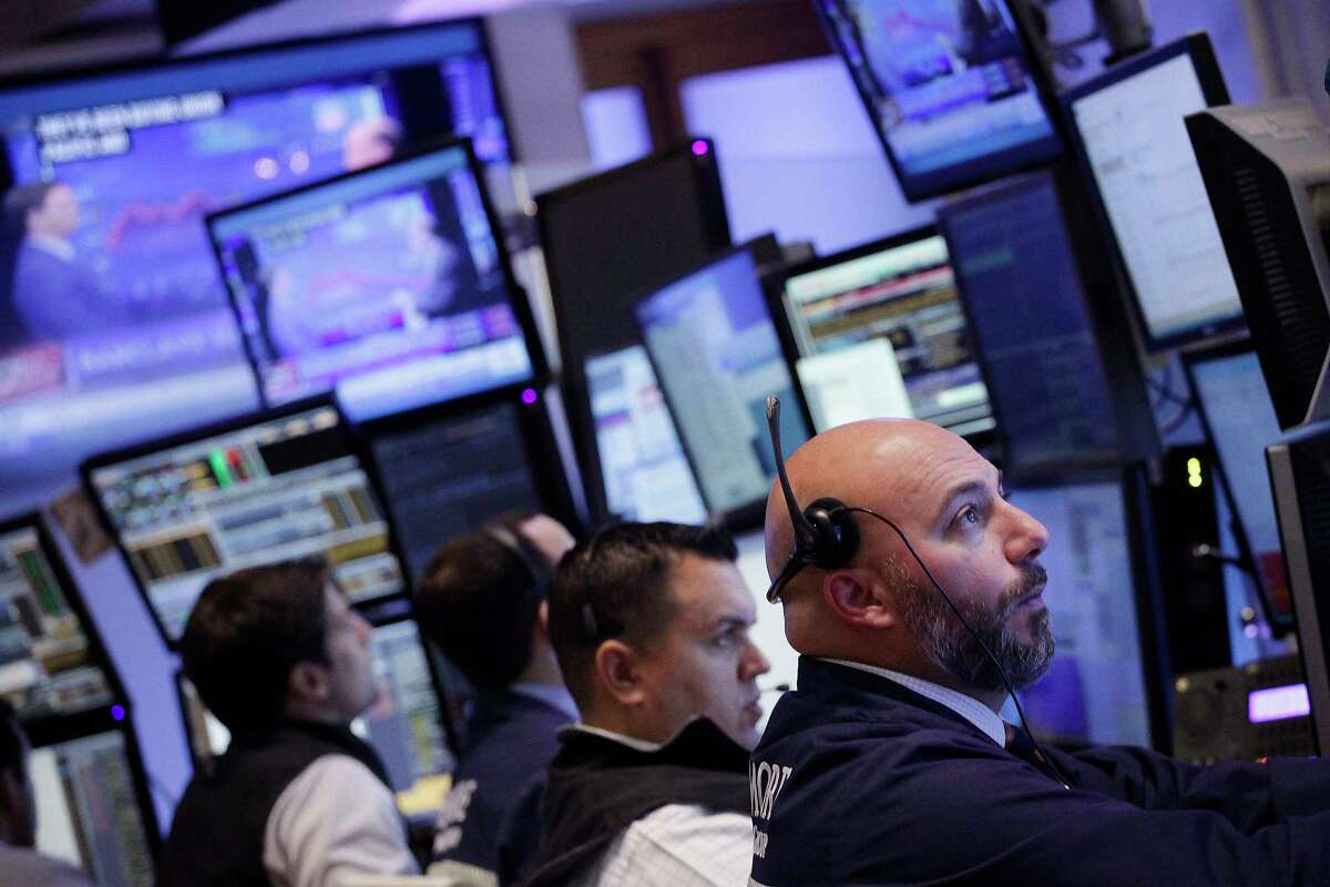 Stock traders work at the New York Stock Exchange Monday.