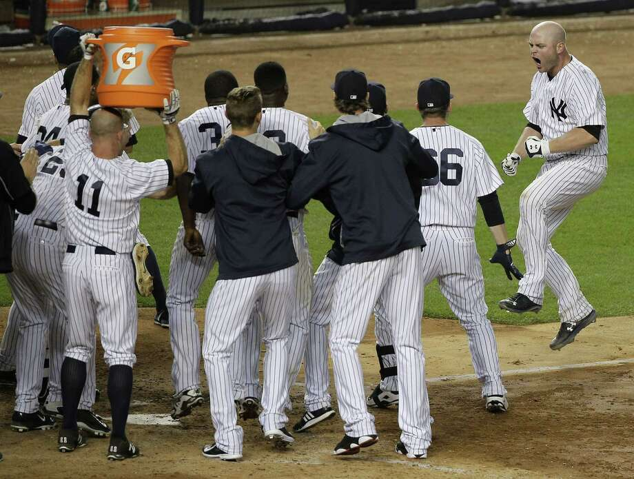 The Yankees' Brian McCann, right, jumps into a crowd of teammates who greet him at home plate after McCann hit a three-run home run against the Tampa Bay Rays in the 12th inning. The Yankees won 7-5. Photo: Julie Jacobson  — The Associated Press   / AP