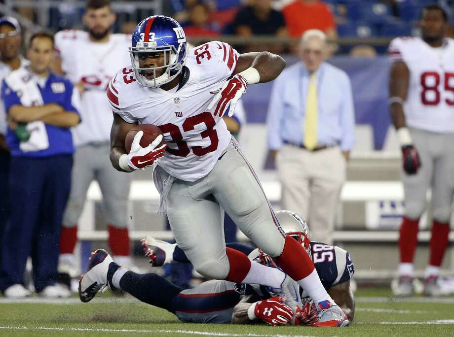 Giants running back Kenneth Harper (33) eludes Patriots linebacker Darius Fleming in the second half Thursday. Photo: Winslow Townson — The Associated Press   / FR170221 AP