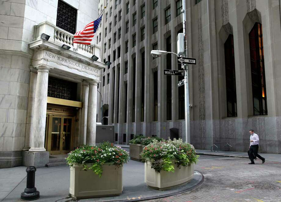 In this Aug. 24, 2015 photo, a man walks towards the New York Stock Exchange. World stocks rose Monday after weak U.S. jobs data prompted expectations the Federal Reserve might postpone an interest rate hike. Photo: AP Photo/Seth Wenig   / AP