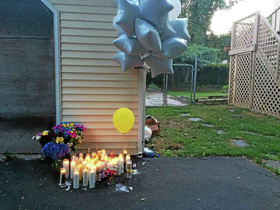 A memorial had sprung up Tuesday night at the house where two people were found dead late Monday. Photo: MARK ZARETSKY — NEW HAVEN REGISTER