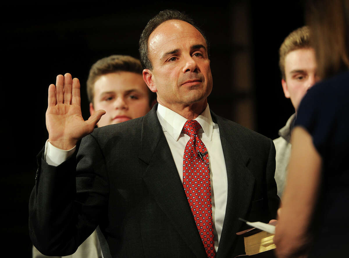 Joseph Ganim is sworn in as Bridgeport mayor as his sons Robert, left, and Joseph, watch, as the Bible is held my his mother Josephine during a ceremony at the Klein Memorial Auditorium Tuesday, Dec. 1, 2015, in Bridgeport. Ganim, a former mayor of Bridgeport, who spent seven years in federal prison for public corruption, was sworn in again on Tuesday as mayor of Connecticut's largest city.