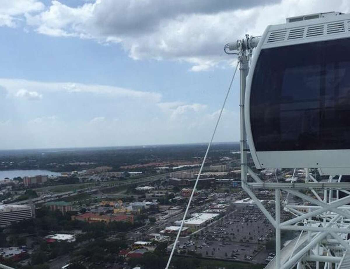 In this photo provided by Makayla Bell, the Ferris wheel known as the Orlando Eye is stopped Friday, July 3, 2015, in Orlando, Fla. Authorities say the 400-foot Ferris wheel stopped moving for more than 45 minutes, stranding riders aboard. (Makayla Bell via AP)