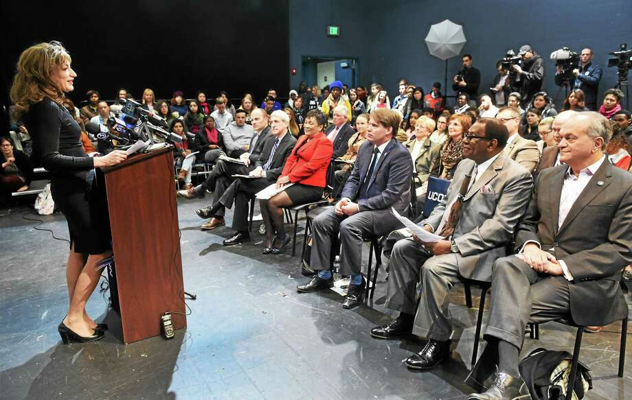 University of Connecticut President Susan Herbst, left, announces the school's participation in the New Haven Promise scholarship program Tuesday. Also in attendance were, seated front row, from left, New Haven Superintendent of Schools Garth Harries, Yale President Peter Salovey, Mayor Toni Harp, state Rep. Roland Lemar, former New Haven Superintendent of Schools Reginald Mayo and former Mayor John DeStefano Jr. Photo: Peter Hvizdak — New Haven Register   / ©2015 Peter Hvizdak
