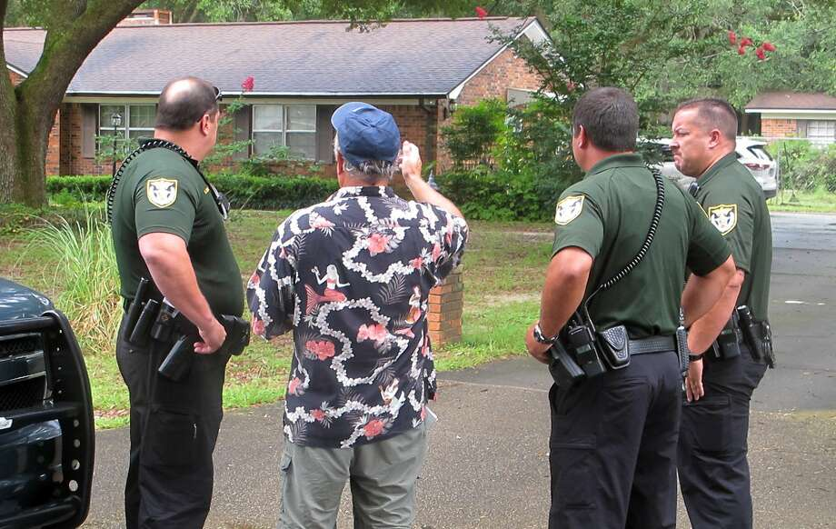 Escambia County Sheriffís deputies talk with an unidentified man on Wednesday, Aug. 5, 2015, outside the Pensacola-area home where three family members were found dead July 28. Escambia County Sheriff David Morgan has said investigators believe the three may have been victims of a ritualistic killing. Photo: AP Photo — Melissa Nelson-Gabriel  / AP