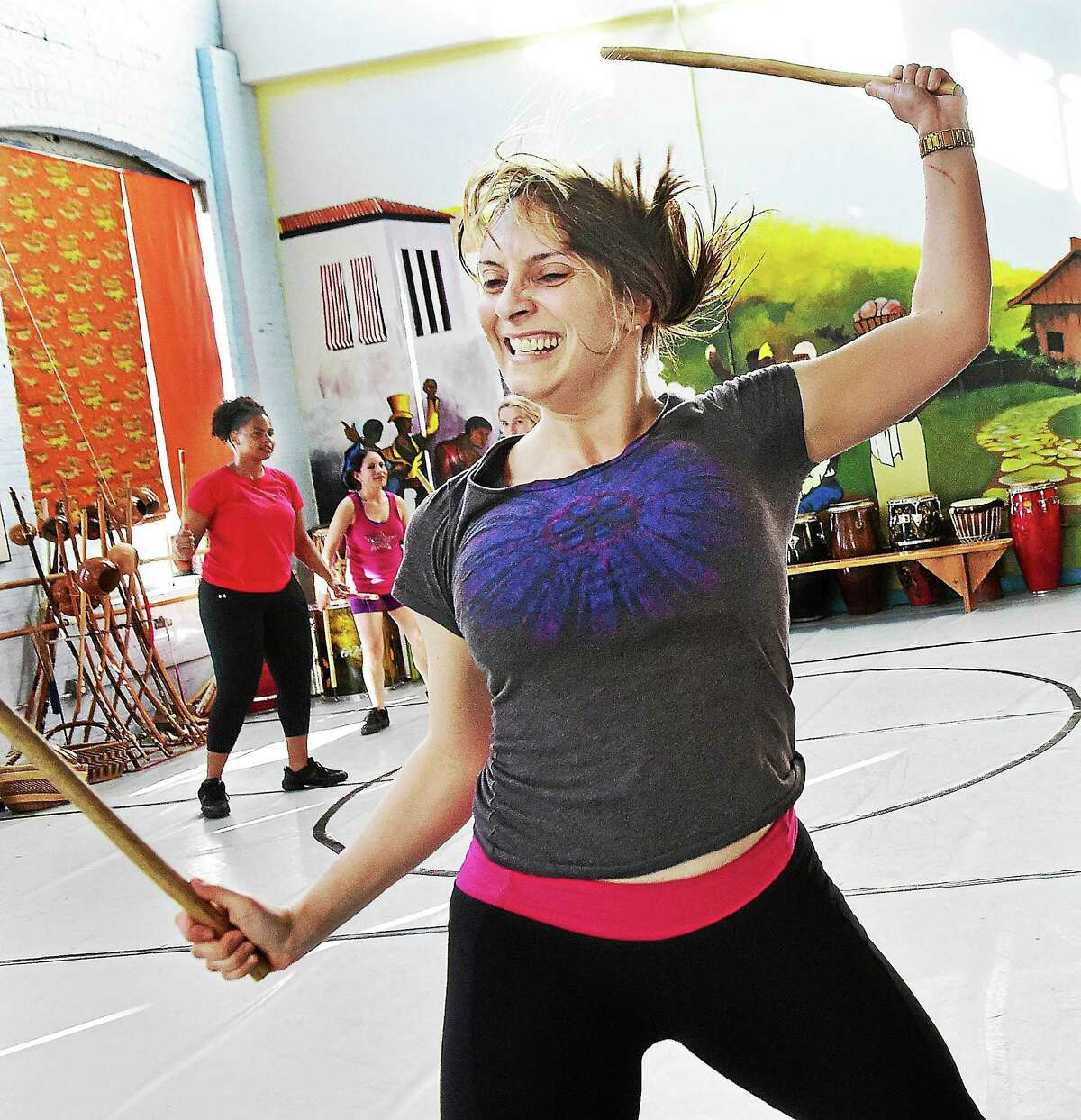 Thelma Ladeira leads members of the samba class, Kristina Douglass, of New Haven and Lina Klaus, of North Haven in the samba class in the maculele or stick dance, a form of African-Brazilian dance, Thursday, June 25, 2015, at Connecticut Capoeira Dance Center in New Haven.
