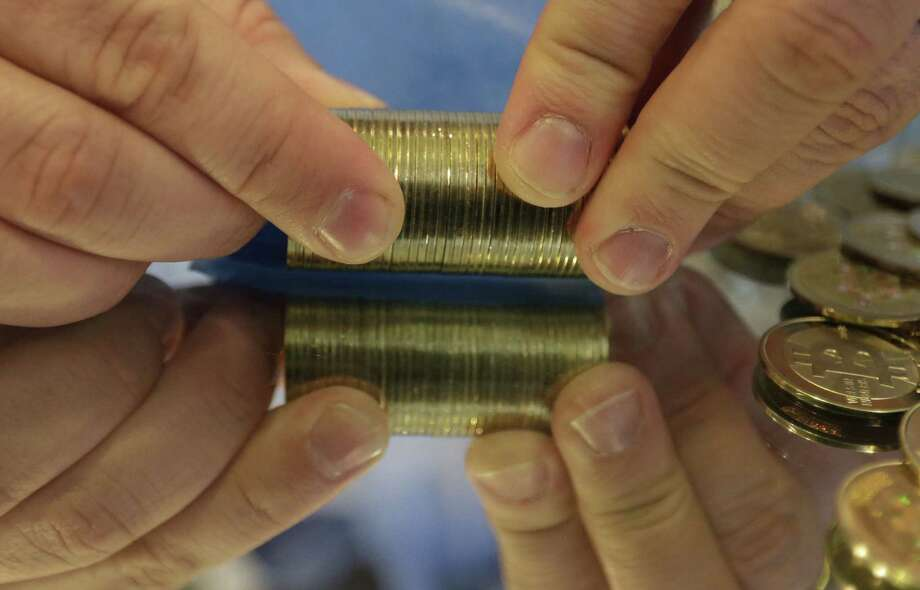 In this April 3, 2013 photo, Mike Caldwell, a 35-year-old software engineer, rolls a stack of bitcoin tokens at his shop in Sandy, Utah. Photo: Rick Bowmer, AP Photo   / AP2013