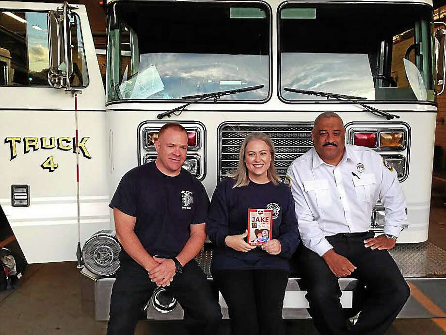 Brigid Buchheit Carney (center), Timothy Carney (left), and Captain Gary Tinney at Dixwell Fire Station. Photo: Ryan Flynn — New Haven Register