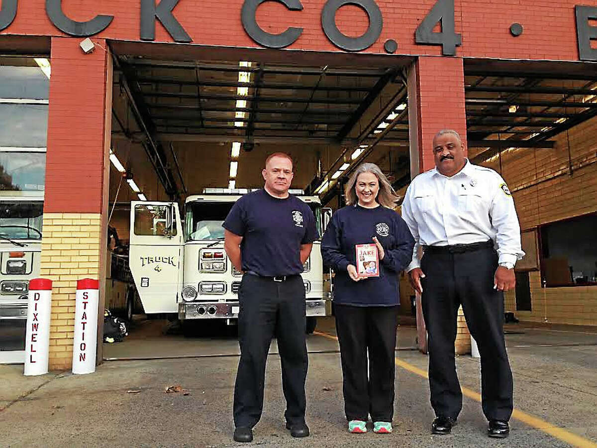 Brigid Buchheit Carney (center), Timothy Carney (left), and Captain Gary Tinney at Dixwell Fire Station.