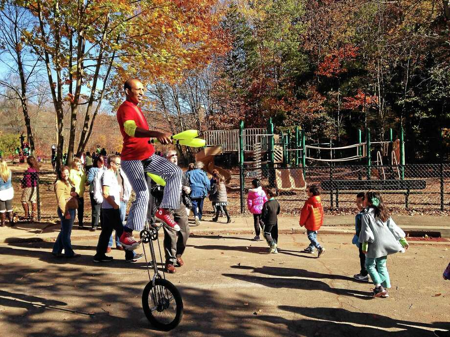 Kate Ramunni -- Register  A unicylist entertains on day one of the new playground at West Woods School. Photo: Journal Register Co.
