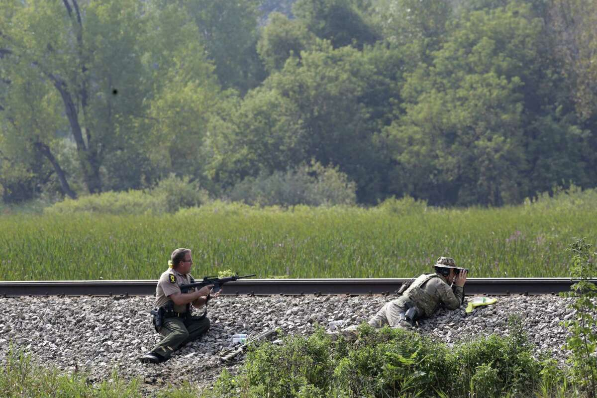 Police officers patrol a swampy area in Fox Lake, Ill., during a manhunt after an officer was shot and killed while pursuing a group of suspicious men, Tuesday, Sept. 1, 2015. Authorities in Fox Lake, 55 miles north of Chicago, have notified a number of other law enforcement agencies to ask for assistance, including the FBI, which is sending agents to help in the investigation.