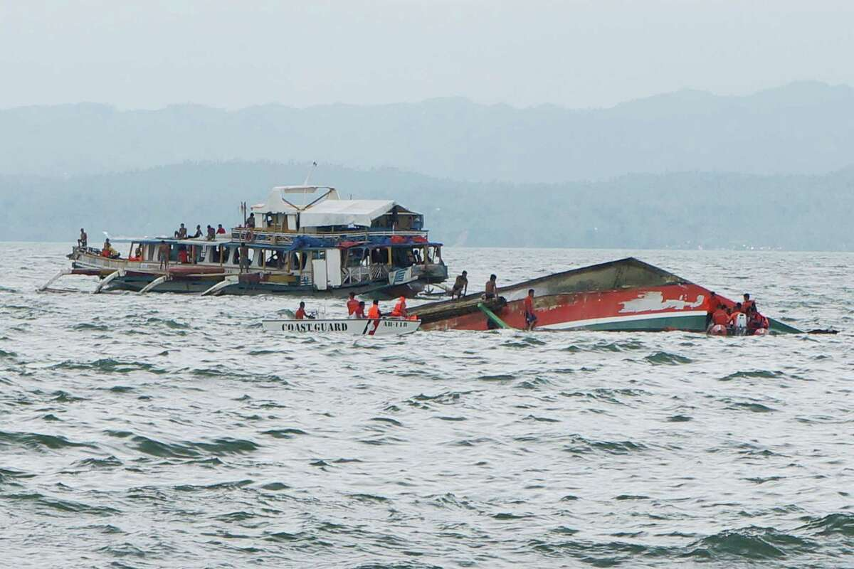 Rescuers help passengers from a capsized ferry boat, right, in Ormoc city on Leyte Island, Philippines, Thursday, July 2, 2015. A ferry capsized Thursday as it left a central Philippine port in choppy waters, leaving dozens dead and many others missing, coast guard officials said. (Ignatius Martin/Miquicar Photostudio via AP)