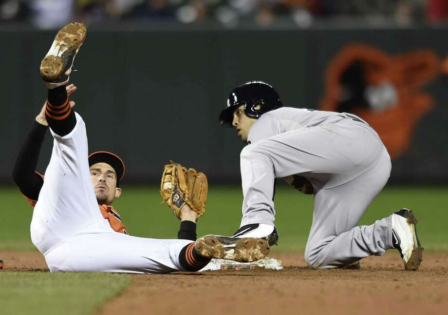 Orioles second baseman Ryan Flaherty, left, falls backward after tagging out Yankees pinch runner Rico Noel in the ninth inning Saturday. Photo: Gail Burton — The Associated Press   / FR4095 AP
