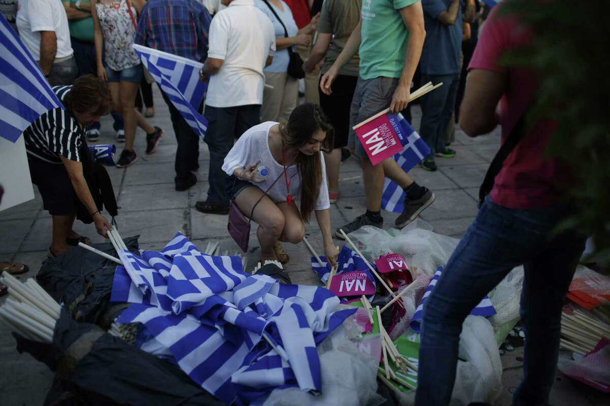A woman takes a flag for free, reading ''Yes to Greece, Yes to Euro'' during a rally organized by supporters of the Yes vote in Athens, Friday, July 3, 2015. A new opinion poll shows a dead heat in Greece's referendum campaign with just two days to go before Sunday's vote on whether Greeks should accept more austerity in return for bailout loans. (AP Photo/Emilio Morenatti)