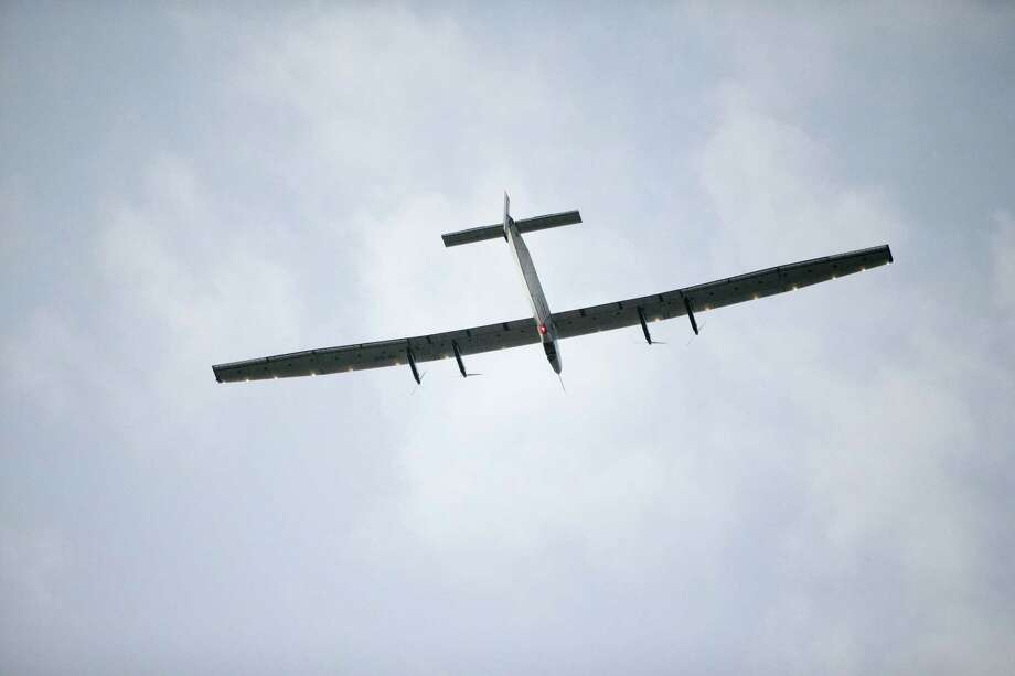 The Solar Impulse 2, a solar-powered airplane, circles the Kalaeloa Airport, Friday, July 3, 2015, in Kapolei, HI.  The plane, piloted by Andre Borschberg, is attempting to fly around the world without fuel.  (AP Photo/Marco Garcia) Photo: AP / FR132415 AP