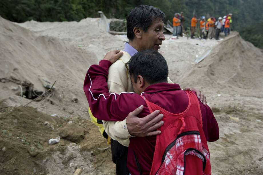 Neighbors comfort each other as rescue workers continue the search at the site of a landslide in Cambray, a neighborhood in the suburb of Santa Catarina Pinula, about 10 miles east of Guatemala City, Saturday, Oct. 3, 2015. The hill that towers over Cambray collapsed late Thursday after heavy rains, burying several houses with dirt, mud and rocks.  The death toll rose to 30 amid fears that hundreds more could still be buried in the rubble. Photo: (AP Photo/Moises Castillo) / AP