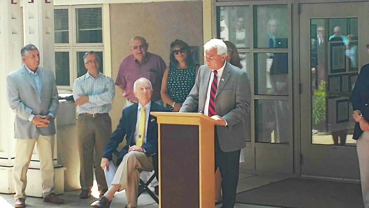 With Madison First Selectman Fillmore McPherson looking on, Thomas Banisch announces his candidacy to fill seat McPherson is vacating, Thursday, July 2, 2015.