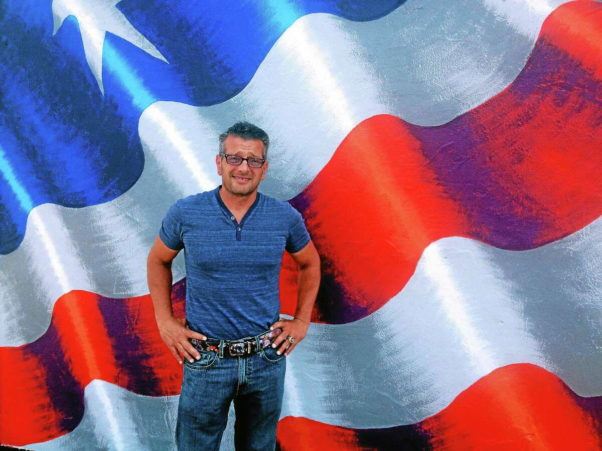 """Artist Scott LoBaido stands in front of one of his flags during his """"Painting Flags Across America, Celebrating America, Thanking Our Veterans Tour,"""" in Milford recently."""