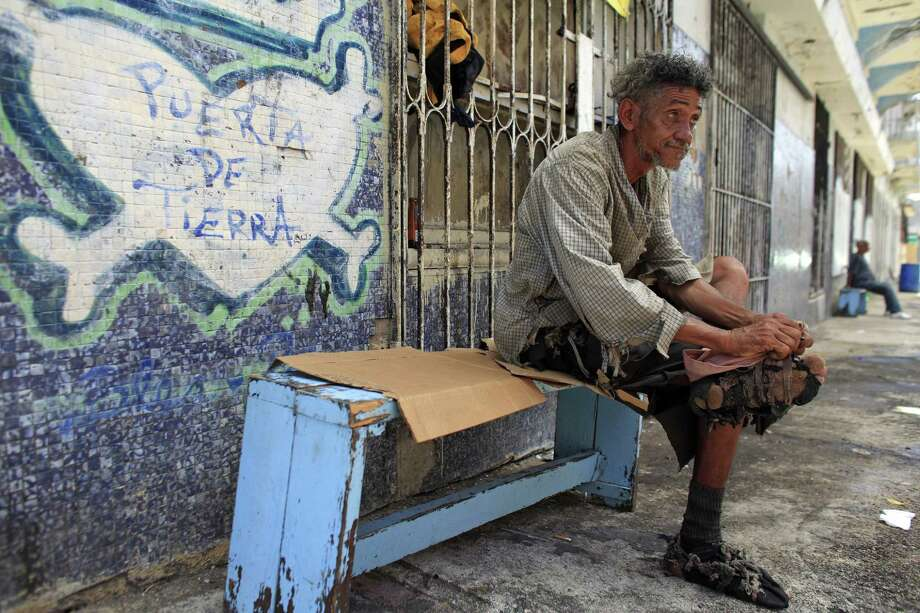 A homeless man improvises his shoes with pieces of cloth in front of a closed down business in Puerta de Tierra in the outskirts of Old San Juan, Puerto Rico. Photo: Ricardo Arduengo — The Associated Press   / AP