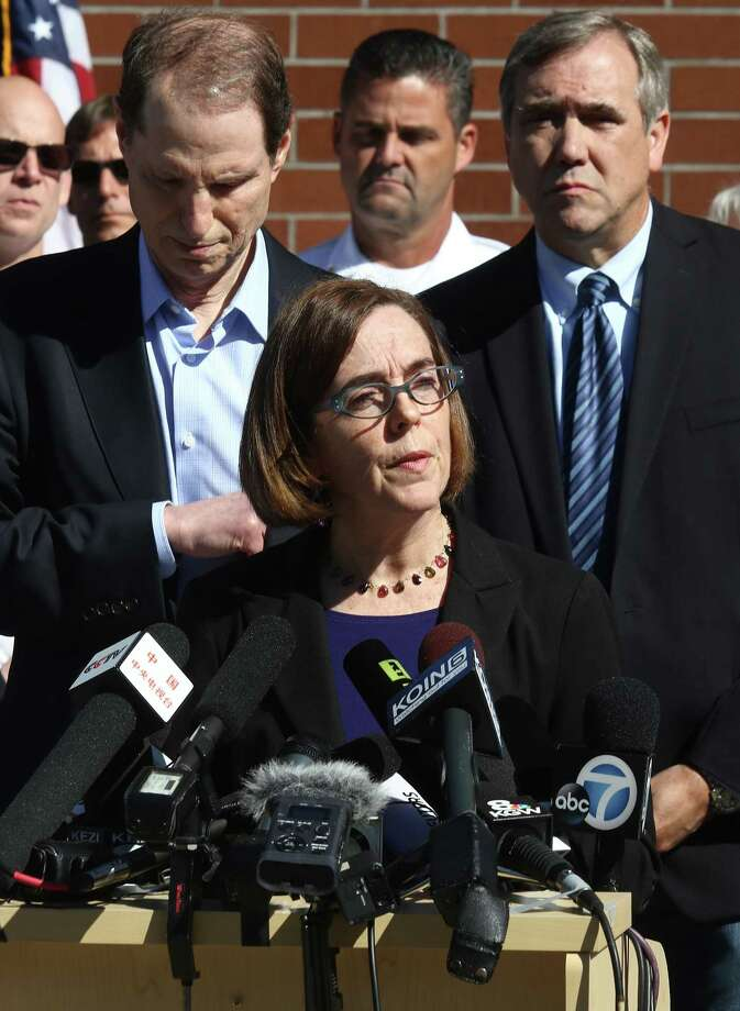 Oregon Gov. Kate Brown, flanked by Sen. Ron Wyden, left, and Sen. Jeff Merkley, addresses the media during a news conference Friday, Oct. 2, 2015, in Roseburg, Ore, regarding the deadly shooting at at Umpqua Community College. Photo: Michael Sullivan/The News-Review Via AP    / The News-Review