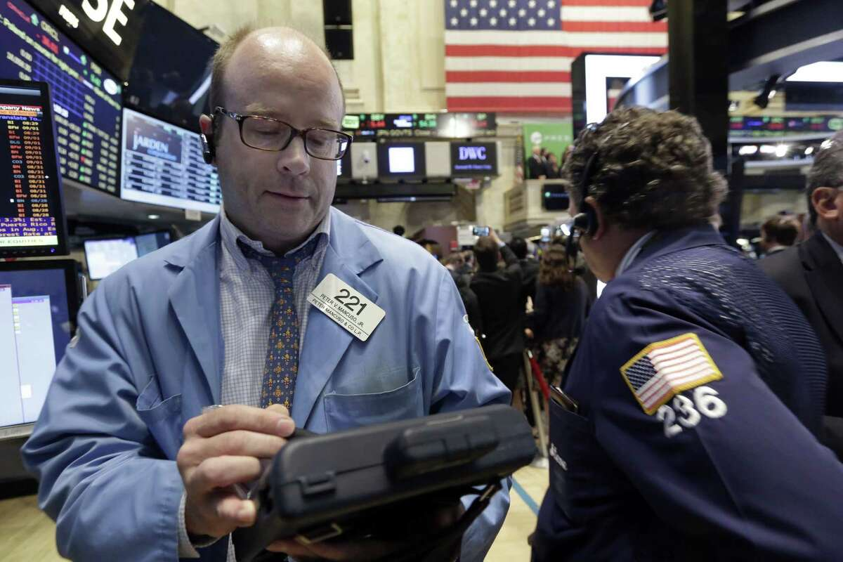 Trader Peter Mancuso, left, works on the floor of the New York Stock Exchange Wednesday.