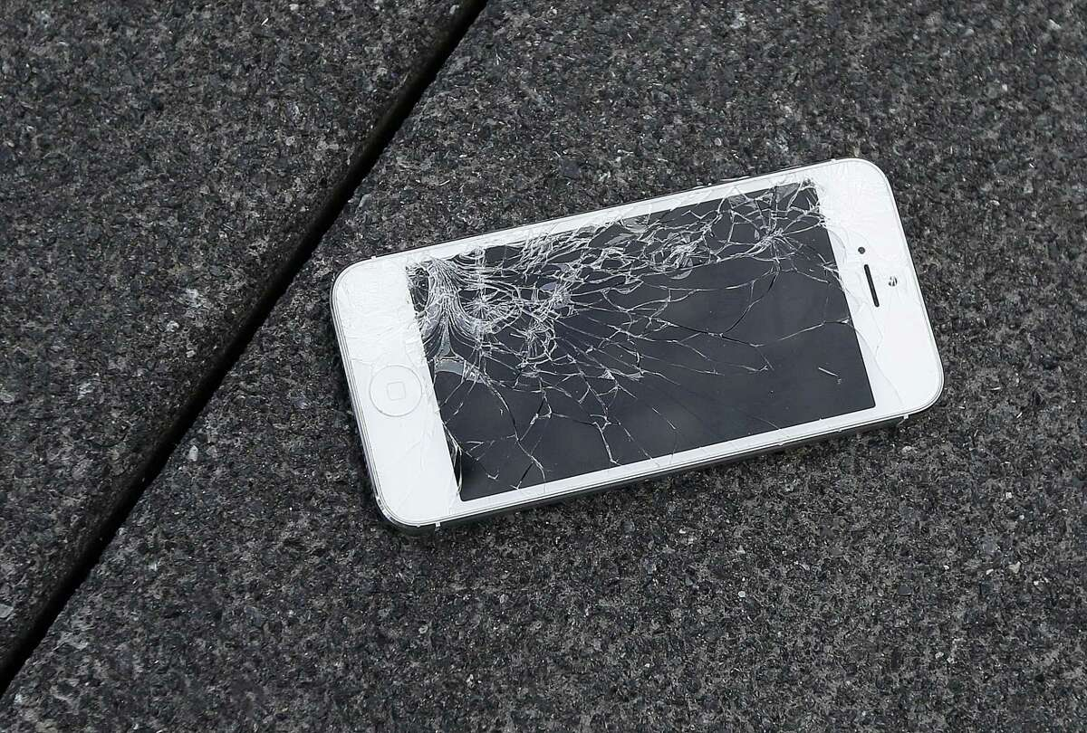 An Apple iPhone with a cracked screen after a drop test from the DropBot, a robot used to measure the sustainability of a phone to dropping, at the offices of SquareTrade in San Francisco.