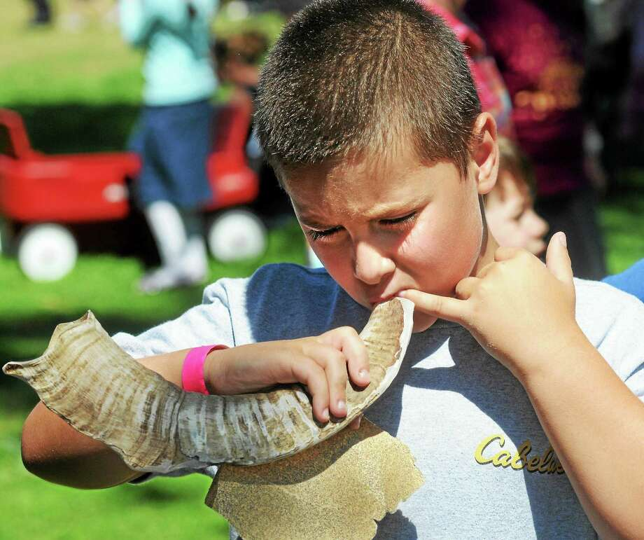 At a previous Shoreline Jewish Festival on the Guilford Green, Danny White of Branford tries to blow through the shofar he just made of a ram's horn. Photo: Mara Lavitt - Register File Photo