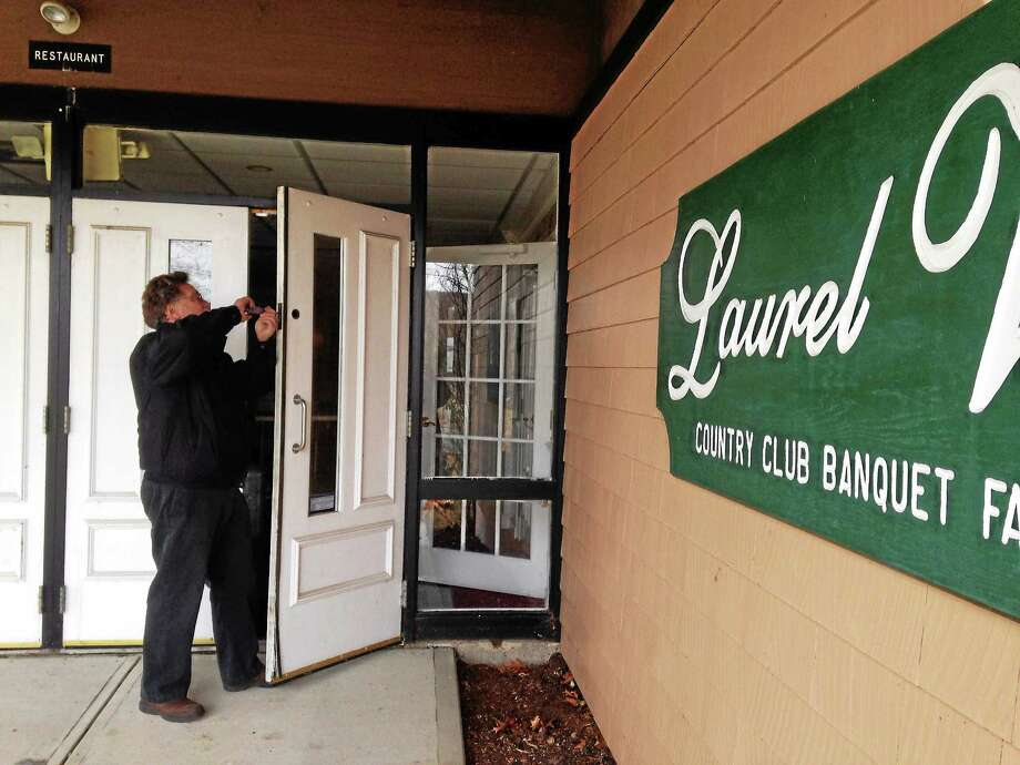 A locksmith prepares to lock the doors at the Laurel View Country Club banquet facilities after operator Eli's was evicted by the town. Photo: Kate Ramuni — New Haven Register