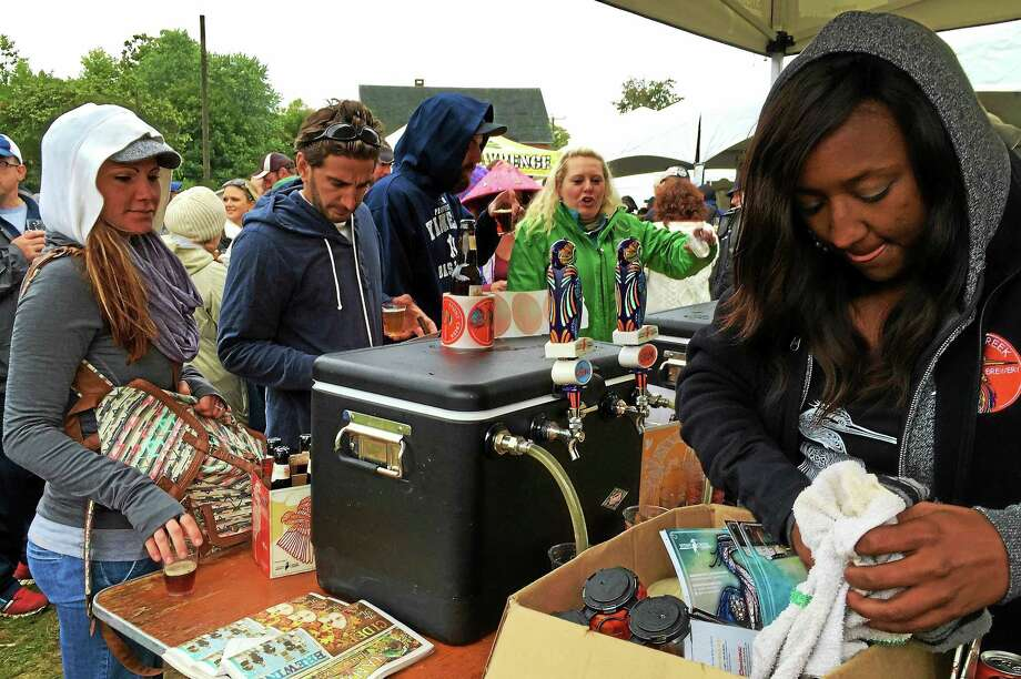 A staffer at the Stony Creek Brewing Company table looks for a drink coaster at the Smoke in the Valley Festival on Saturday, Oct. 3, in Seymour. Stony Creek, a Branford-based brewery, was one of several local breweries handing out samples on Saturday. Photo: Esteban L. Hernandez — New Haven Register