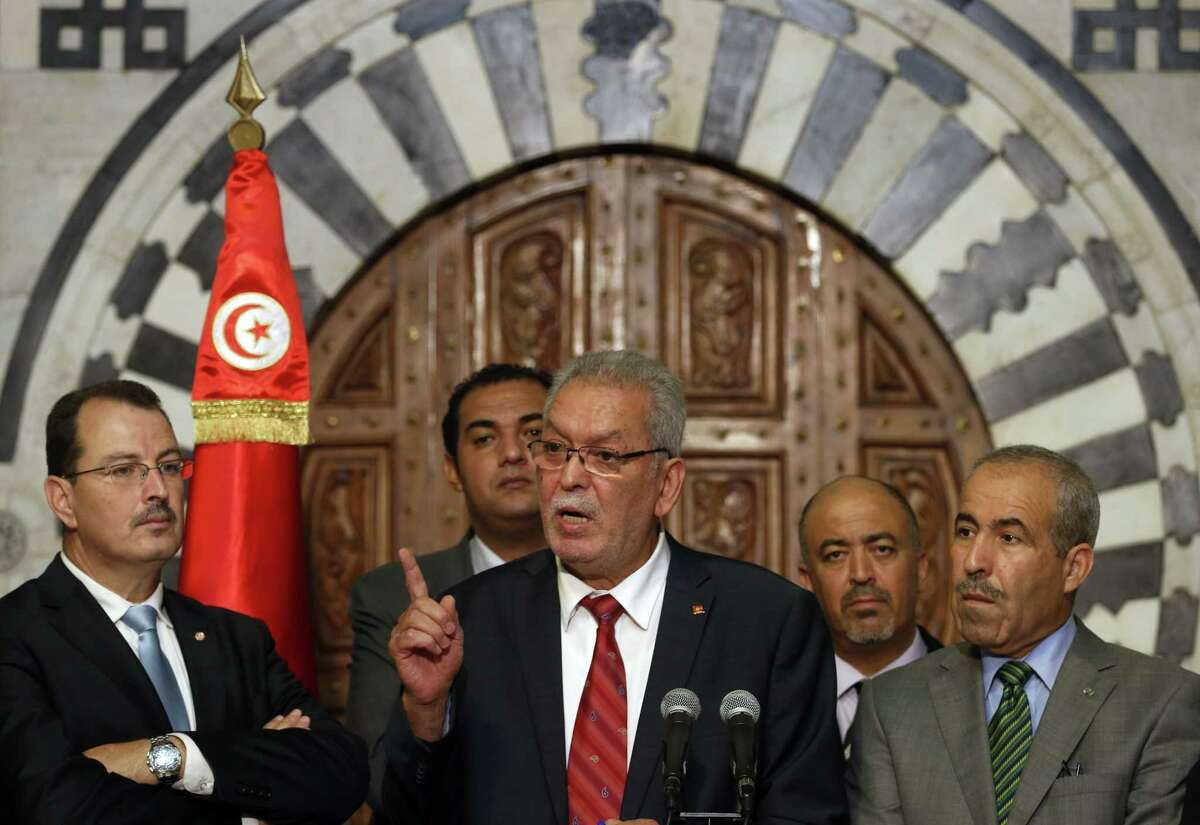 Kamel Jendoubi, Minister to the Prime Minister in charge of Relations with Constitutional Bodies and the Civil Society, center speaks during a press conference in Tunis, Tunisia, Thursday, July 2, 2015. The Islamic State group claimed responsibility for the attack, in which a Tunisian student opened fire on a beach in the resort of Sousse. The attacker was later killed by police. (AP Photo/Darko Vojinovic)