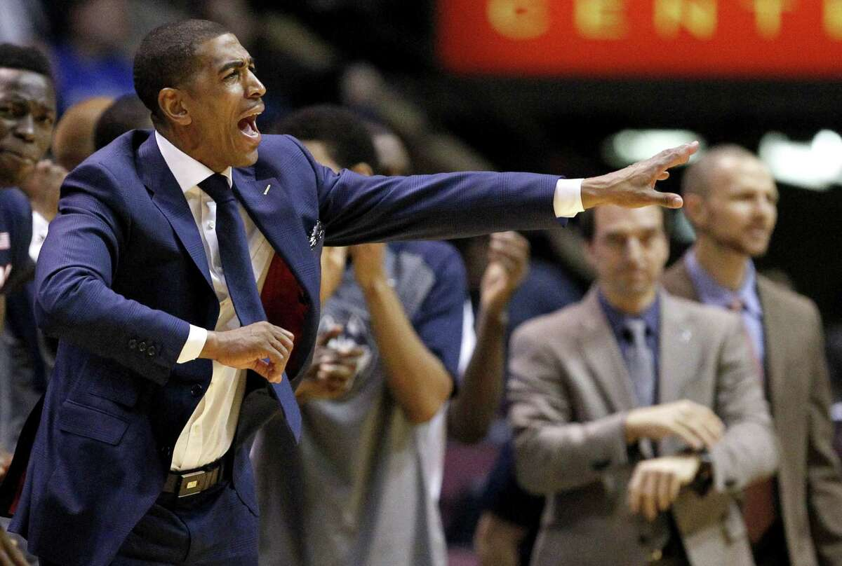 Connecticut head coach Kevin Ollie, left, talks to his team during the first half of an NCAA college basketball game against Duke, Thursday, Dec. 18, 2014, in East Rutherford, N.J. Duke won 66-56. (AP Photo/Julio Cortez)