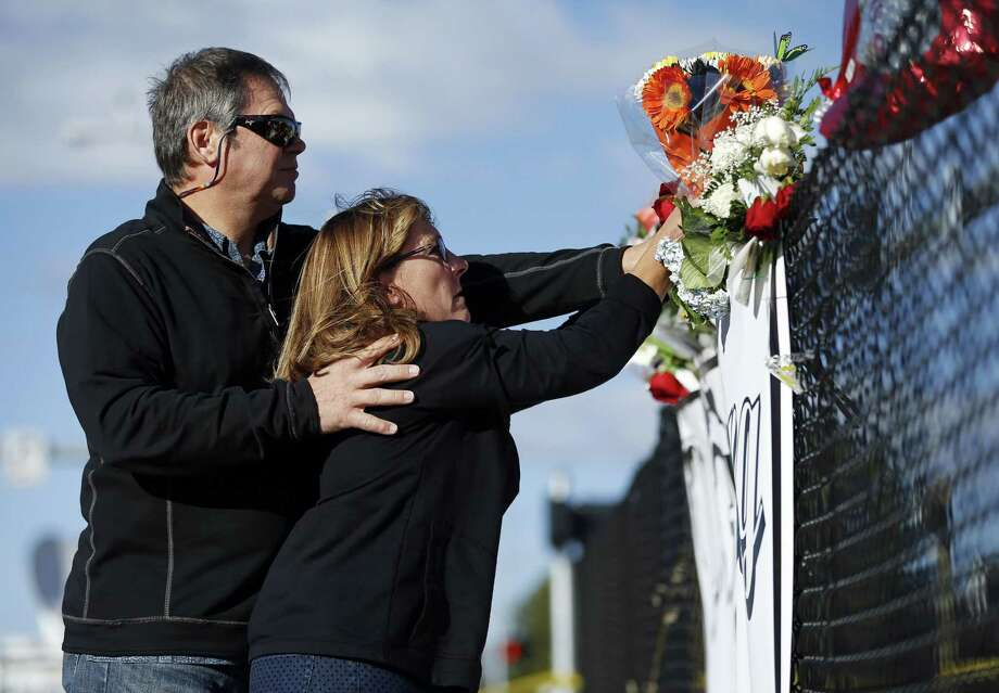 Charley Thompson, left, and his wife Rachel Thompson place flowers at a makeshift memorial near the road leading to Umpqua Community College, Saturday, Oct. 3, 2015, in Roseburg, Ore. Armed with multiple guns, Chris Harper Mercer walked in a classroom at the community college, Thursday, and opened fire, killing several and wounding several others. Photo: (AP Photo/John Locher) / AP