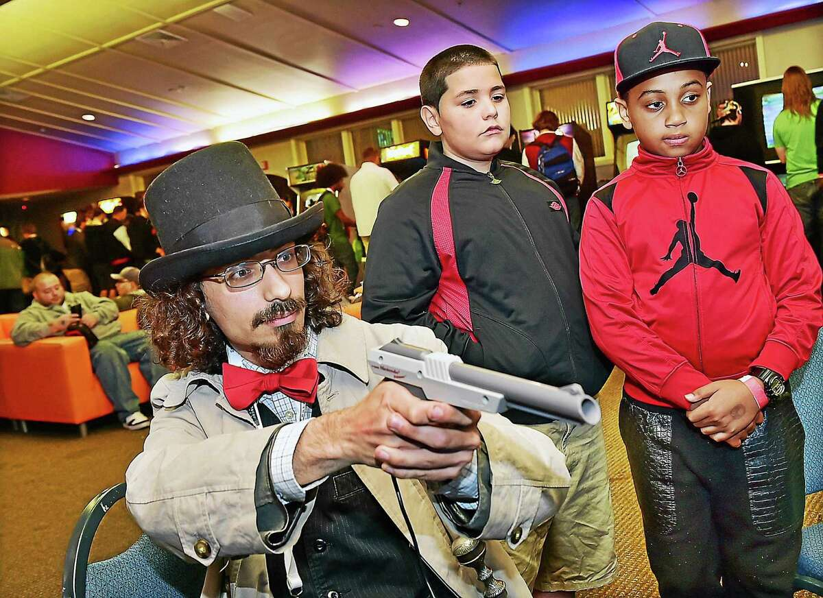 Providence residents Angel Olivencia, 10, center and Carlos Lopez, 8, right, watch Manchester resident David Vold aim the Nintendo Zapper light gun at the monitor while playing the 1984 video game Duck Hunt, Saturday, October 3, 2015, at the RetroWorld Expo at the Oakdale Theater in Wallingford. The objective of the 1984 video game is to shoot moving targets in mid-flight.