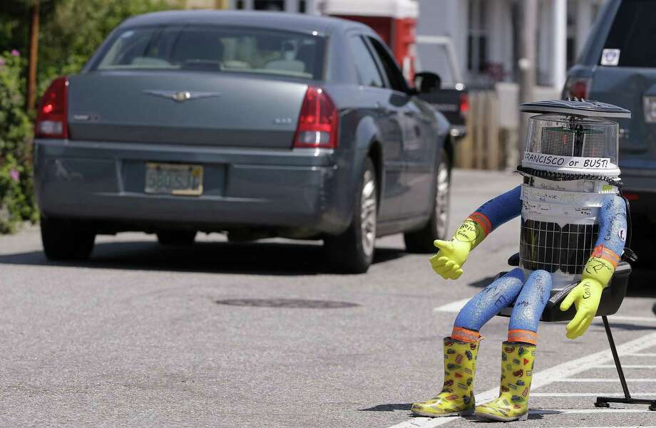In this July 17 photo, a car drives by HitchBOT, a hitchhiking robot in Marblehead, Mass. The Canadian researchers who created hitchBOT as a social experiment say someone in Philadelphia damaged the robot beyond repair on Saturday, ending its brief American tour. The robot was trying to travel cross-country after successfully hitchhiking across Canada last year and parts of Europe. Photo: AP Photo   / AP