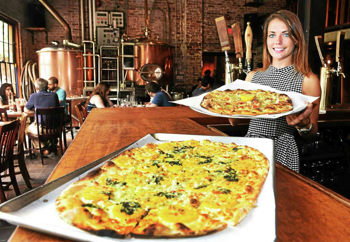 Waitress and bartender Lauren Patrick, daughter of co-owner Frank Patrick, shows off BAR's lobster pizza and fresh heirloom tomato pizza.