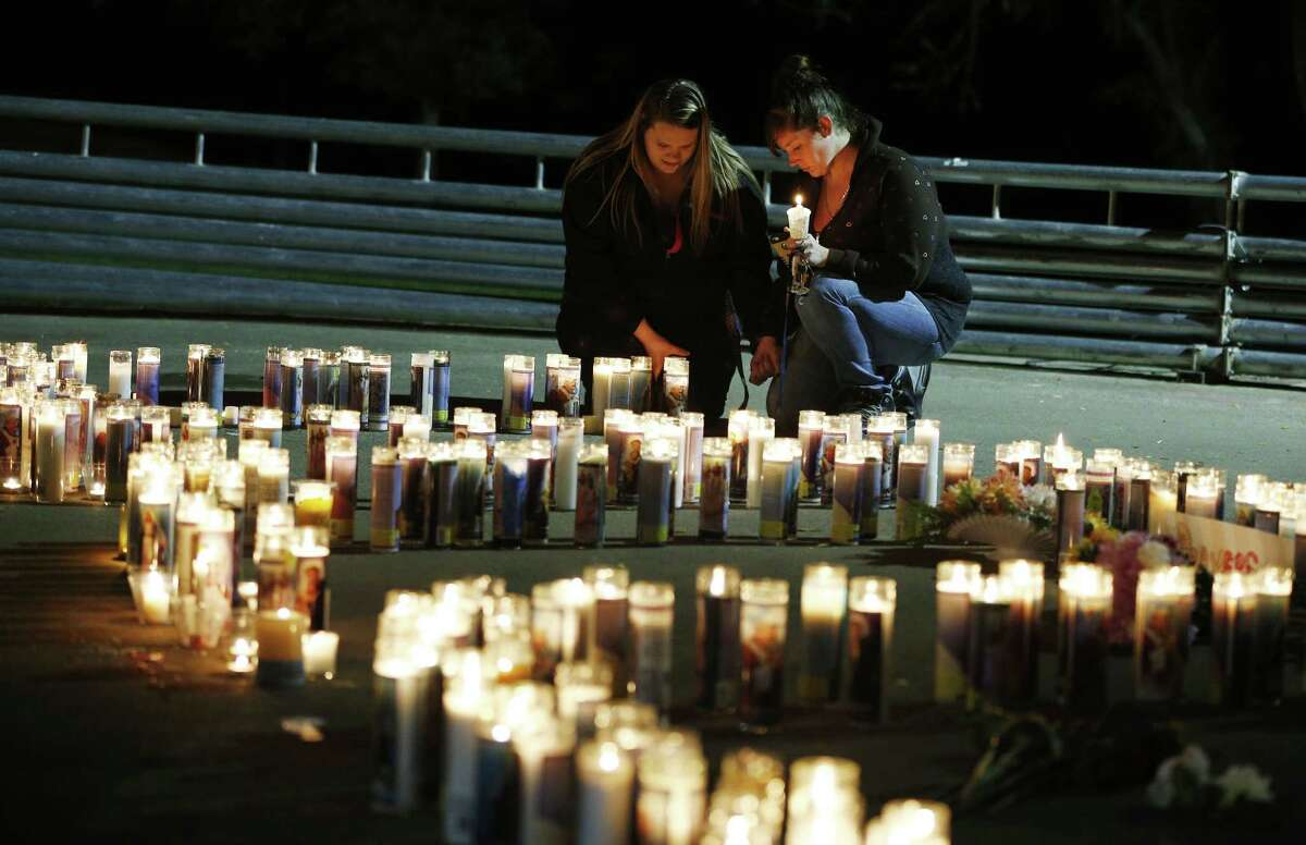 Meriah Calvert, left, of Roseburg, Ore., and an unidentified woman pray by candles spelling out the initials for Umpqua Community College after a candlelight vigil Thursday in Roseburg, Ore.