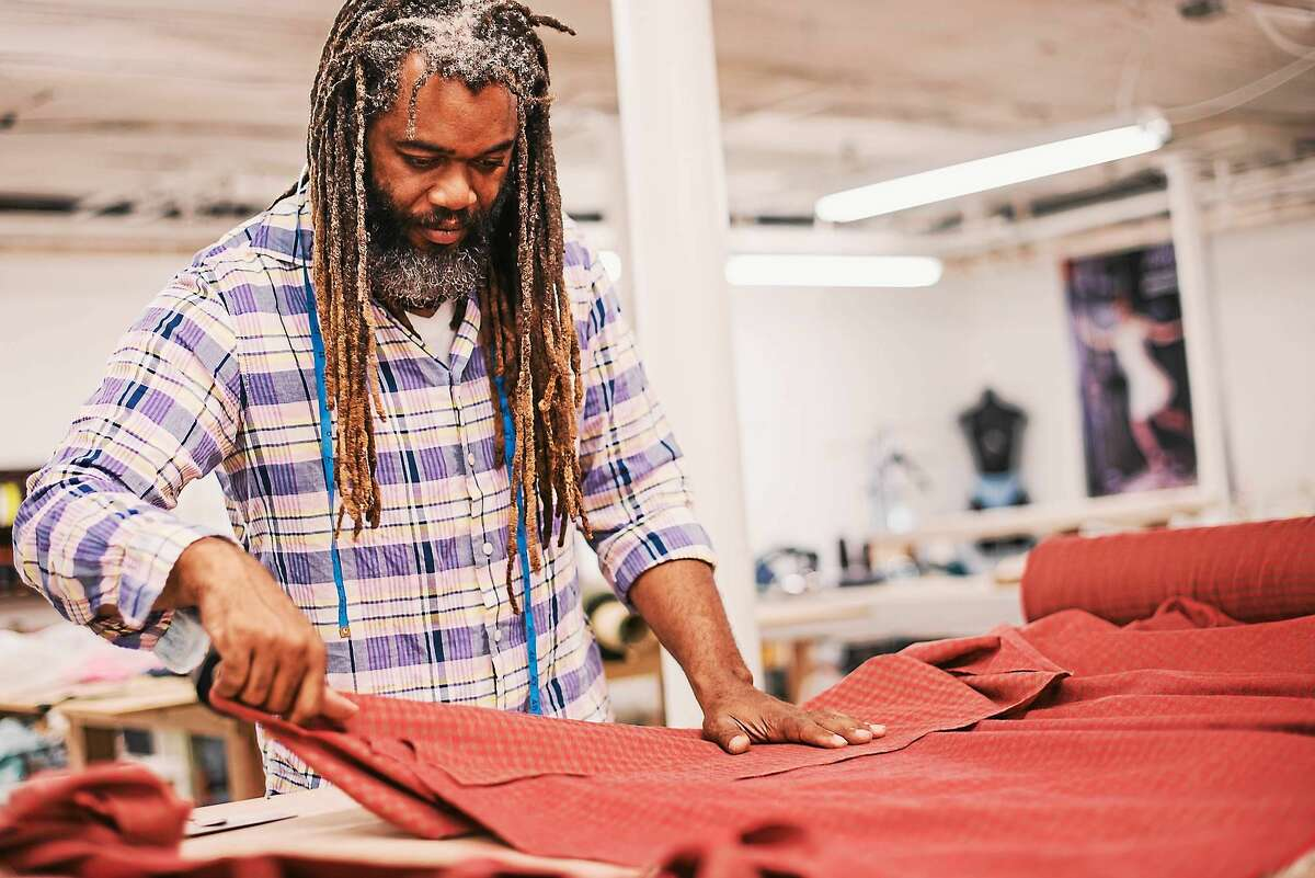 Designer Neville Wisdom works with wool fabric for one of the pieces to be featured in his fall fashion show this week.