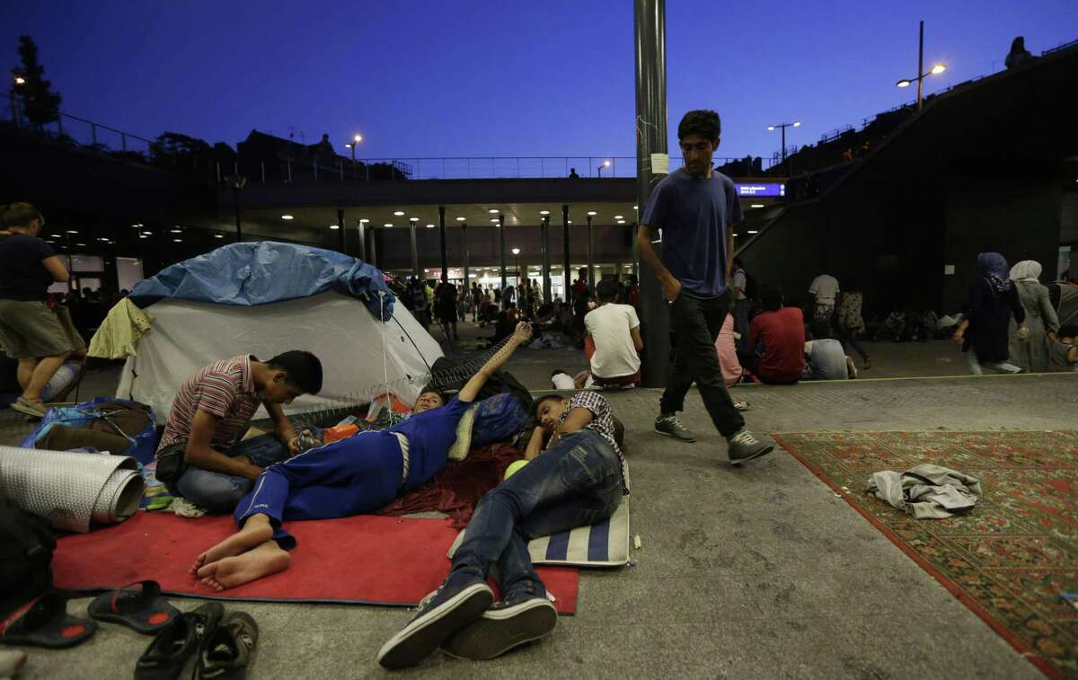 Young men rest as hundreds of migrants wait near the Keleti Railway Station in Budapest, Hungary, Tuesday, Sept. 1, 2015, after police stopped them from getting on trains to Germany.